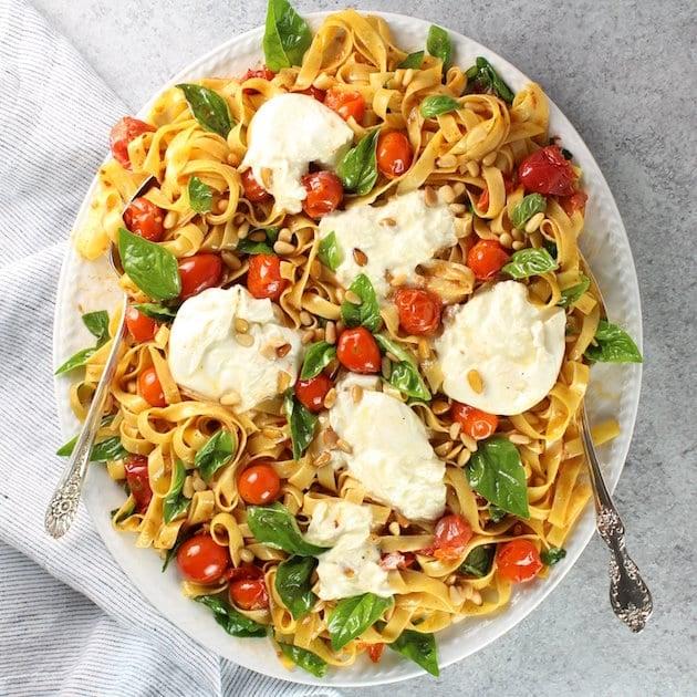 Platter of tagliatelle pasta with tomato, burrata, and basil