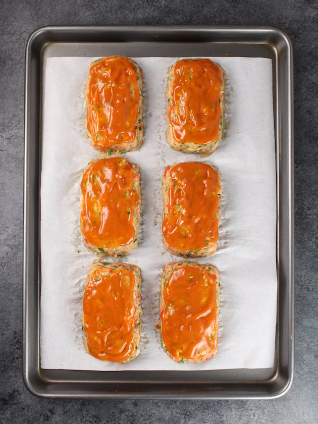 Turkey Meatloaves with sauce on a baking sheet.
