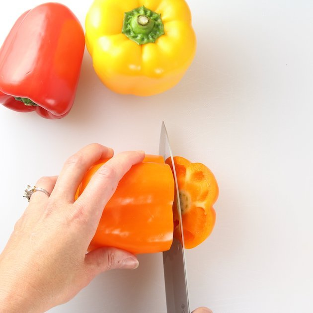 Slicing orange bell pepper on a cutting board