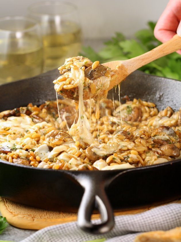 Wooden spoon lifting cheesy scoop of Marsala Chicken Orzo out of a cast iron Skillet