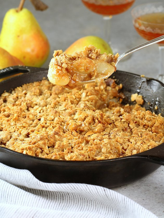 Spoonful of Pear Bourbon Skillet Crisp over full skillet
