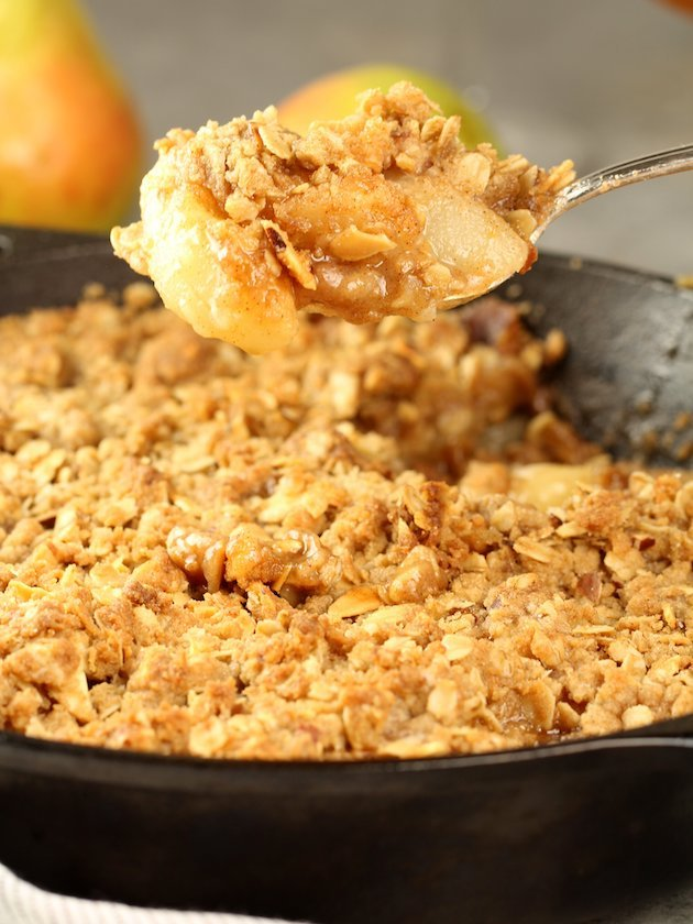 Spoonful of pear crisp over skillet