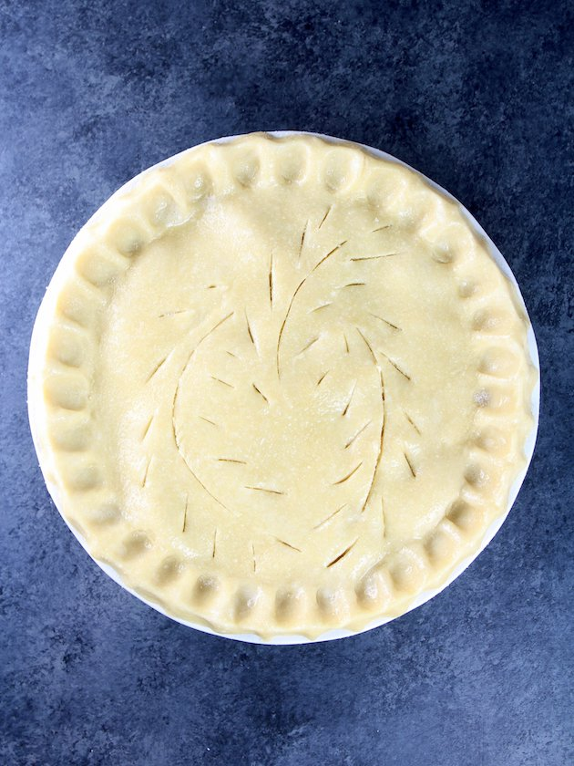 Pie before cooking with crimped edges and whimsical venting cuts on top
