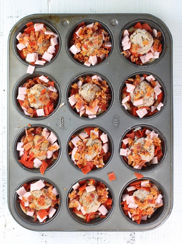 Muffin pan with mini pizzas before cooking