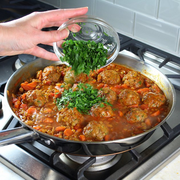 Moroccan Lentils with Turkey Meatballs Recipe & Image - adding parsley to pan of meatballs on stovetop