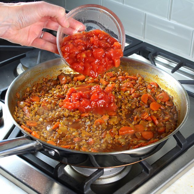 Adding tomatoes to lentils on stovetop