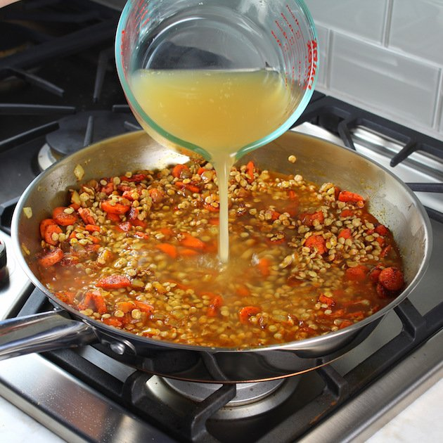 Moroccan Lentils with Turkey Meatballs Recipe & Image - adding stock to pan of lentils stovetop