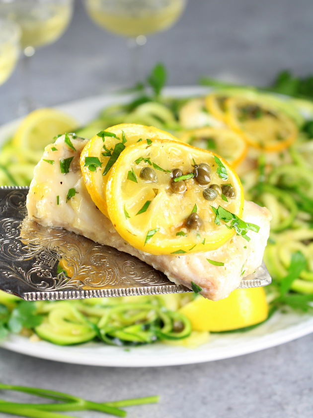 Baked Haddock Fish Piccata with Zucchini Noodles Recipe & Image: Spatula holding cooked haddock