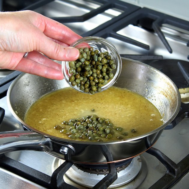 Adding capers to saucepan