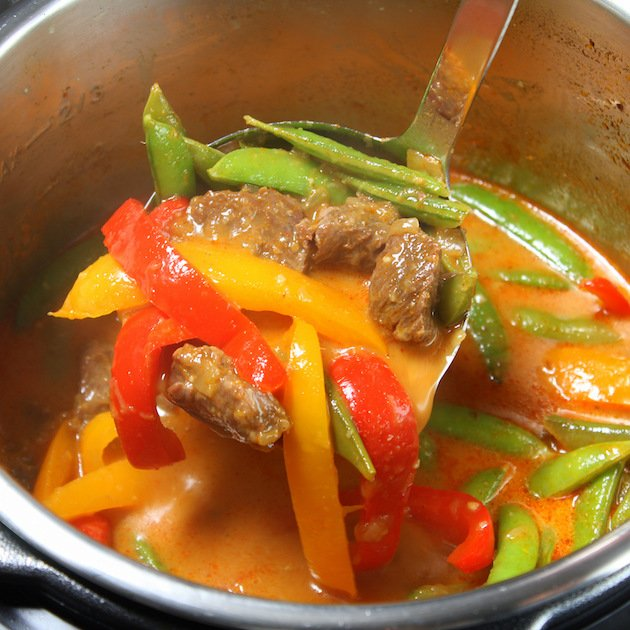 Ladle in a bowl of Instant Pot Beef Thai Red Curry