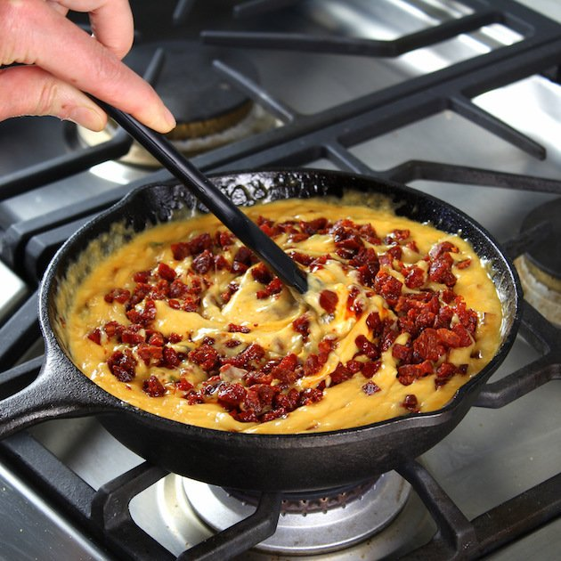 Queso Fundido with Chorizo Recipe and Image - stirring chorizo into pan