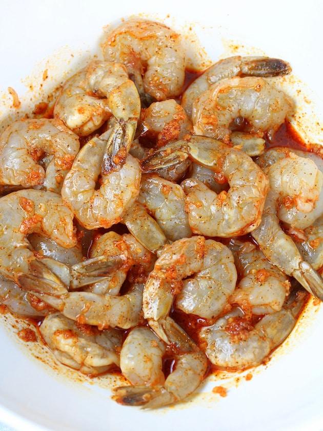 Shrimp in bowl tossed in marinade