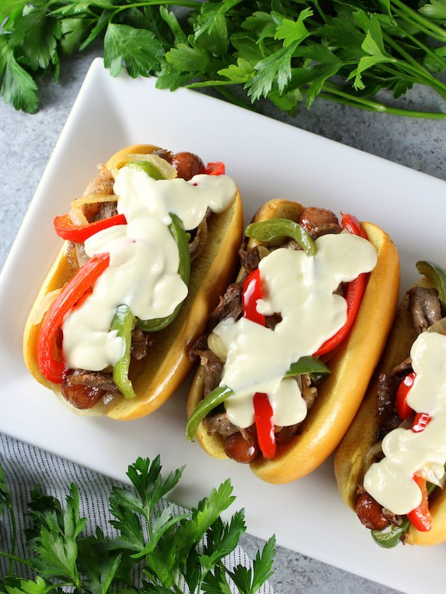 Philly Cheesesteak Hot Dog Recipe & Image: Partial platter of sandwiches with cheese sauce OT