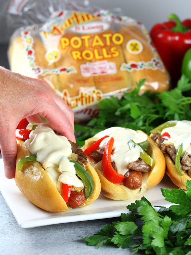 Philly Cheesesteak Hot Dog Recipe & Image: Lifting sandwich with package of rolls in background