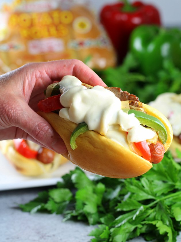 Philly Cheesesteak Hot Dog Recipe & Image: Holding a single cheesesteak dog - up close