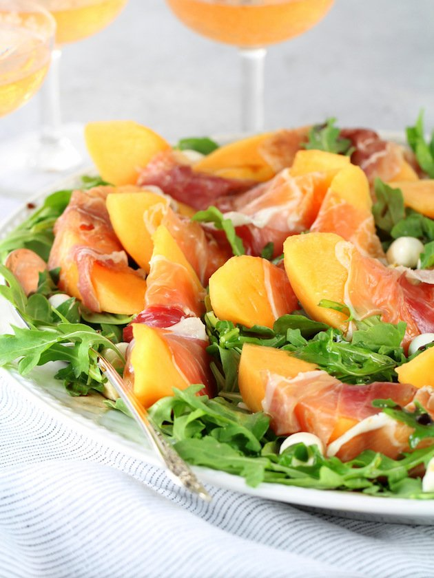Melon Mozzarella Prosciutto Salad with Arugula Recipe & Image: Platter of salad EL with wine glasses