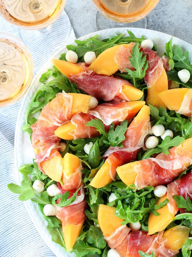 Melon Mozzarella Prosciutto Salad with Arugula Recipe & Image: Platter of salad OT with wine glasses