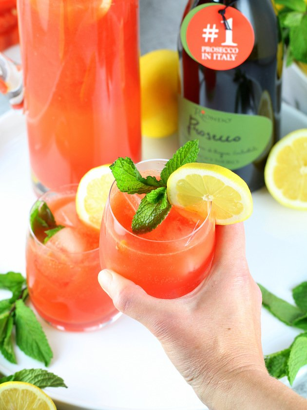 Watermelon Lemonade Prosecco Spritzer Recipe & Image: holding a glass of spritzer