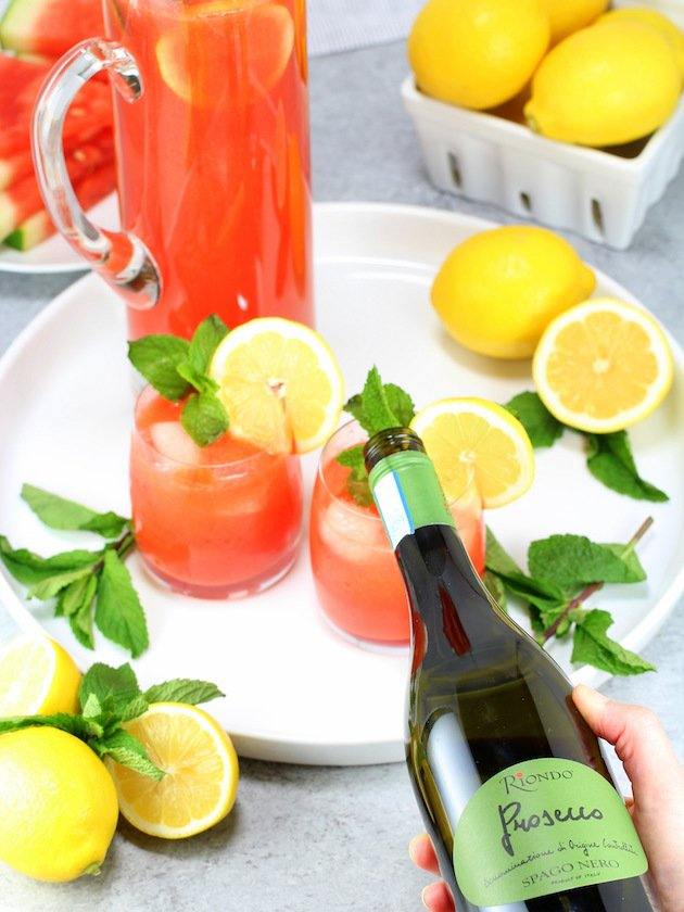 Pouring prosecco into glass of Watermelon Lemonade Prosecco Spritzer