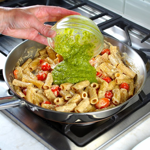 One Pot Creamy Chicken Pesto Pasta Recipe & Image: adding pesto to sun dried tomato chicken pasta