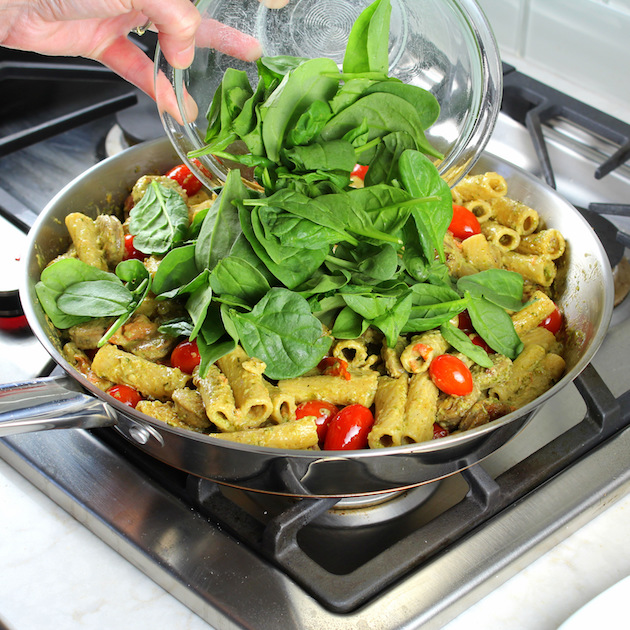 One Pot Creamy Chicken Pesto Pasta Recipe & Image: adding spinach to pesto chicken pasta on stovetop