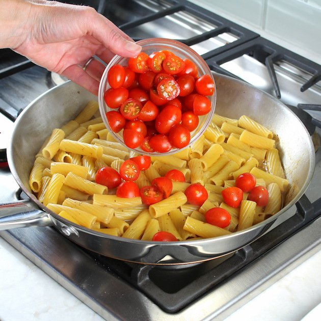 One Pot Creamy Chicken Pesto Pasta Recipe & Image: adding tomatoes to pasta saucepan on stovetop
