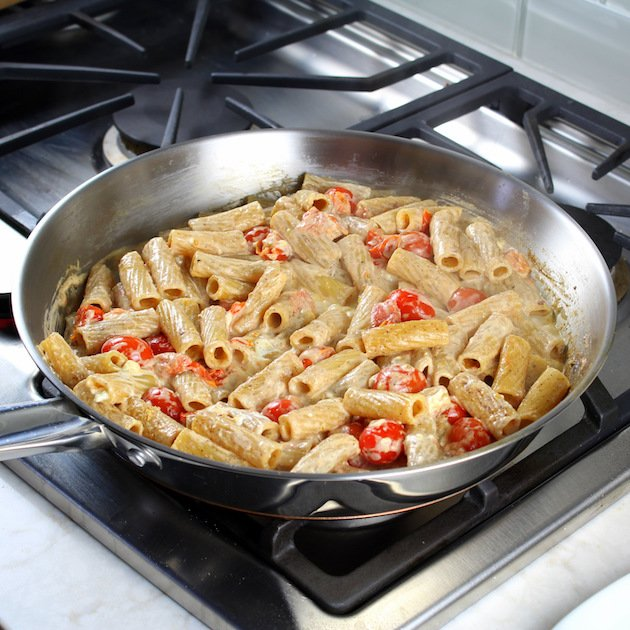 One Pot Creamy Chicken Pesto Pasta Recipe & Image: sun dried tomato chicken pasta cooking on stovetop