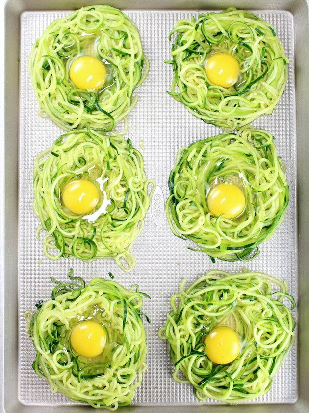 Zoodle Egg Nests Recipe & Image - Zoodle Nests With Uncooked Eggs on cookie sheet