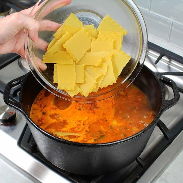 Adding lasagna pasta to soup pot with red sauce