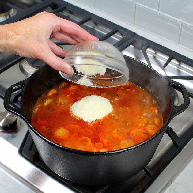 Adding parmesan cheese to soup pot