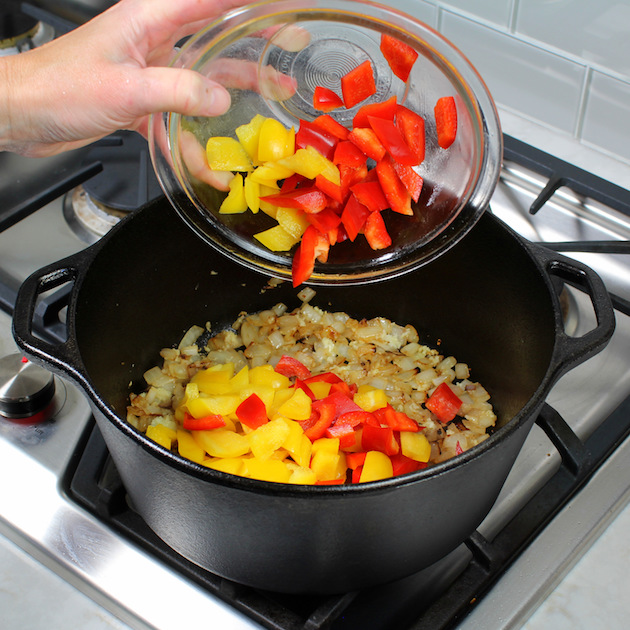 Adding bell peppers to large soup pot on stovetop