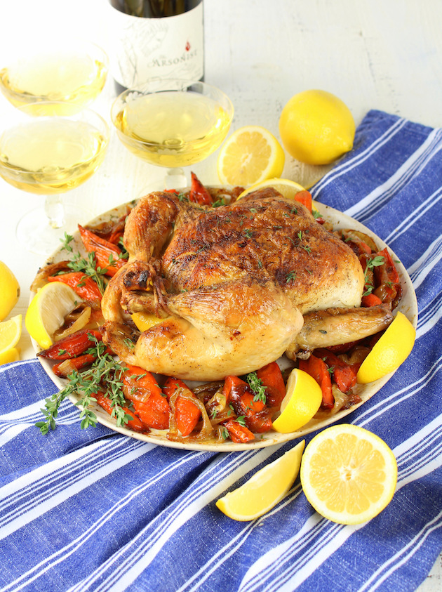Lemon Thyme Oven Roasted Chicken Recipe & Image: Cooked roast chicken on platter with wine glasses