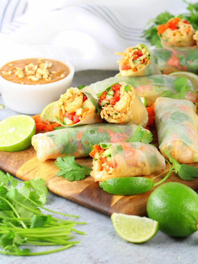 Spring rolls on cutting board with peanut dipping sauce
