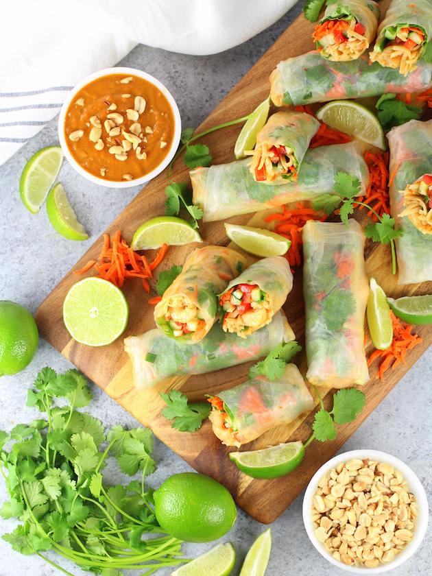 Shrimp rolls on cutting board with bowl of peanut thai sauce