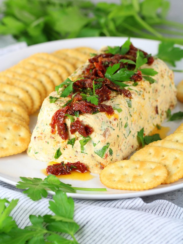 Bacon Ranch Cheese Log Appetizer Recipe and Image - wide shot of cheese log on plate with crackers