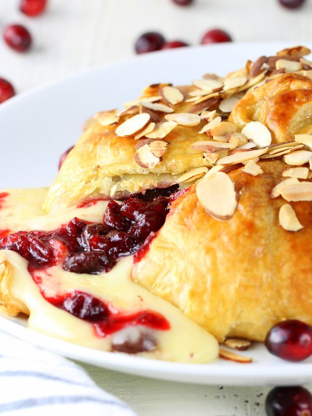 Baked puff pastry brie with cherry Cranberry sauce oozing out