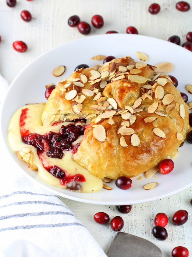 Baked Brie Recipe & Image: Partial platter brie cut open with cranberries & cheese