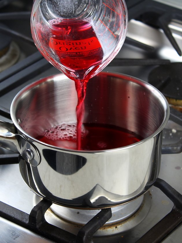 Adding cranberry juice to cooked cranberries on stove
