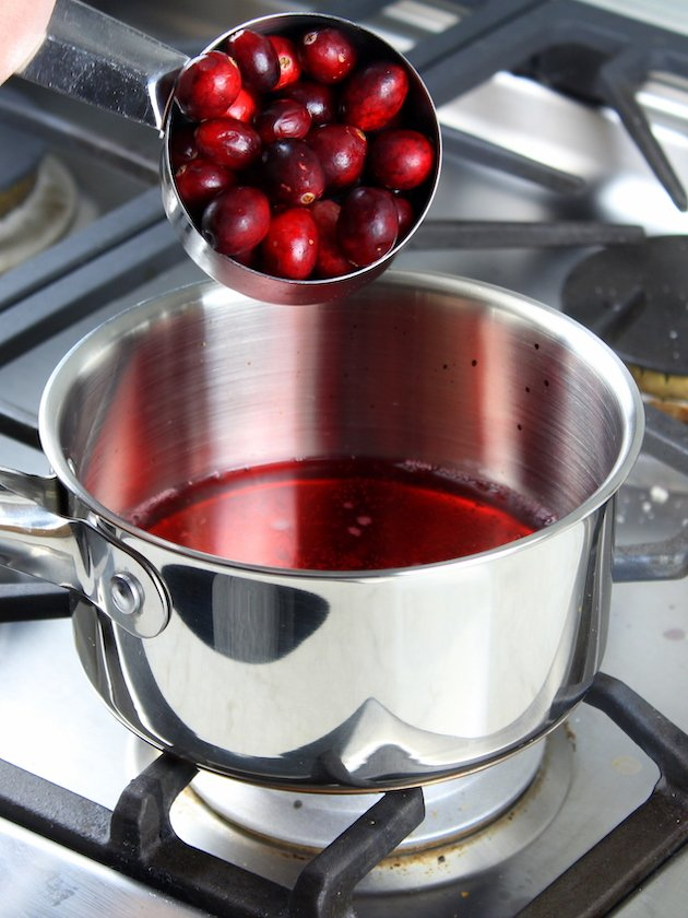 Baked Brie Recipe & Image: Adding cranberries to saucepot on stove