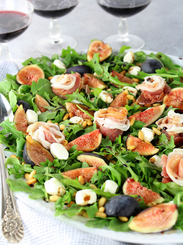 Eye level platter of fig salad with Prosciutto and Mozzarella
