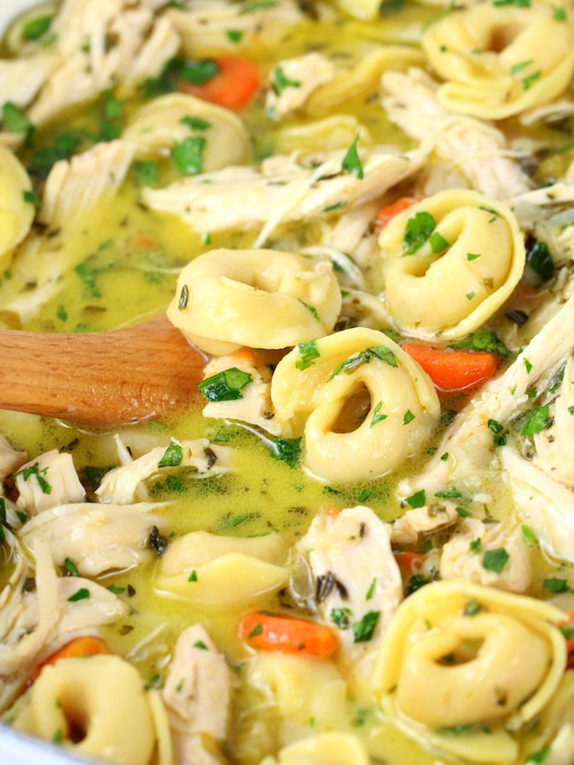 Close up bowl of tortellini soup with chicken