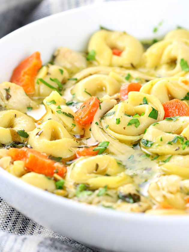 Close up eye level bowl of tortellini soup with chicken