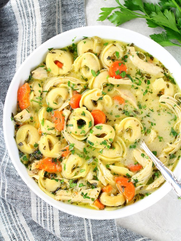 A bowl of tortellini soup with chicken