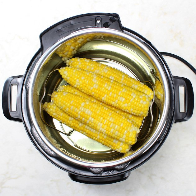 An instant pot with cooked Corn on the cob