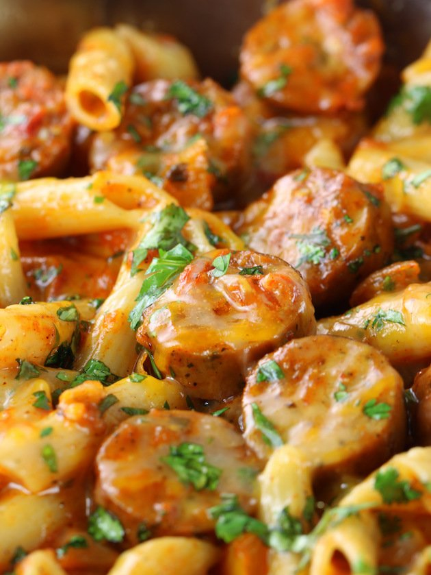 A close up of cheesy pasta with chicken sausage