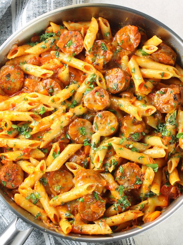 A pan filled with chicken sausage and penne pasta