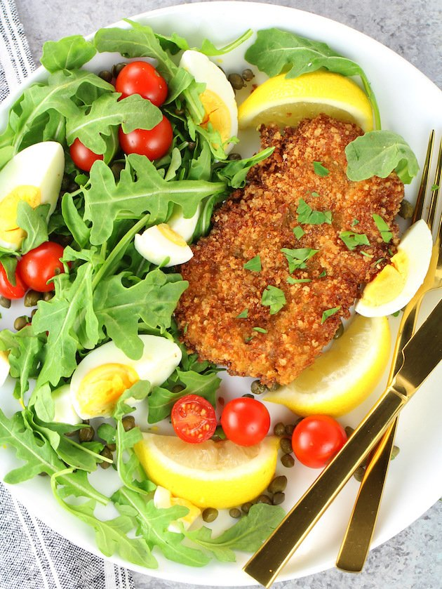 Breaded veal cutlet on a bed of arugula