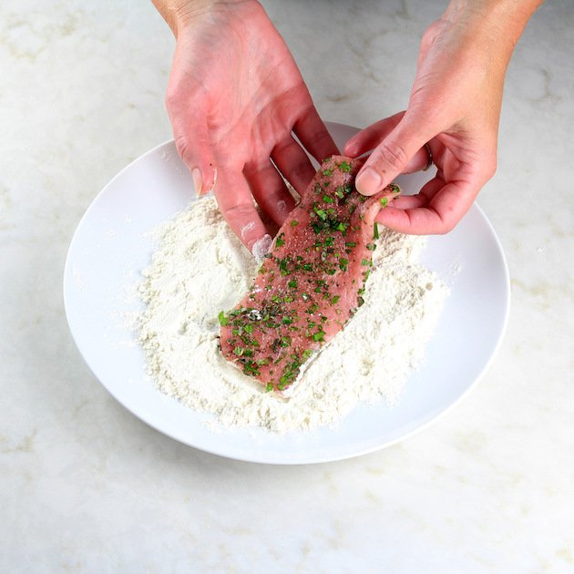 Coating a veal cutlet in flour