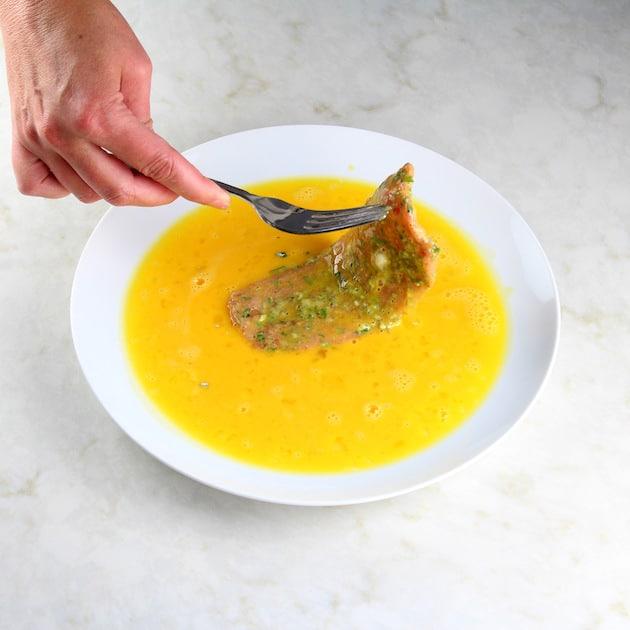 Coating a veal cutlet in egg wash