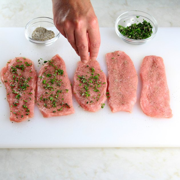 Adding herbs to veal cutlets